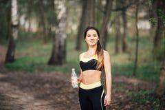 Agua potable sonriente joven de la mujer de la botella después del ejercicio del deporte de la aptitud al aire libre en parque Fotografía de archivo libre de regalías