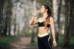 Agua potable sonriente joven de la mujer de la botella después del ejercicio del deporte de la aptitud al aire libre en parque Fotografía de archivo