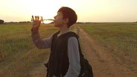 Agua potable turística del adolescente del muchacho de una botella plástica en naturaleza Sed sin hogar del agua de la bebida del Imagenes de archivo