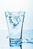 Agua pura que salpica en el vidrio Imagenes de archivo