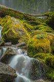 Agua que acomete alrededor de Moss Covered Boulders imagen de archivo
