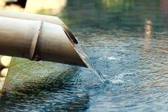 Agua que cae abajo del tubo de bambú Foto de archivo libre de regalías