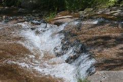 Agua que conecta en cascada abajo de la ladera Fotos de archivo
