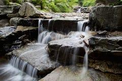 Agua que conecta en cascada sobre rocas. Imagenes de archivo