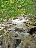 Agua que conecta en cascada sobre rocas en la ensenada de Cades imagen de archivo libre de regalías