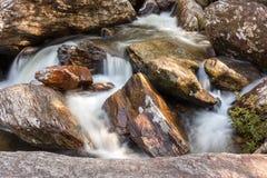 Agua que fluye entre las rocas Imagenes de archivo