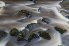 Agua que fluye sobre piedras cerca de la base del invierno de la cascada Imágenes de archivo libres de regalías
