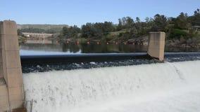 Agua que fluye sobre una presa almacen de metraje de vídeo