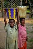 Agua que lleva del niño liberiano Imagen de archivo