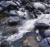 Agua que lucha las rocas Fotos de archivo libres de regalías