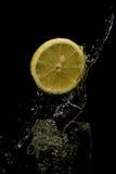 Agua que salpica con el limón. Imagen de archivo