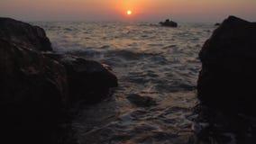 Agua que salpica contra rocas con puesta del sol almacen de metraje de vídeo