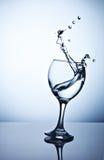 Agua que salpica fuera de una copa de vino alta fotos de archivo
