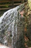 Agua que se derrama sobre roca cubierta de musgo imagenes de archivo