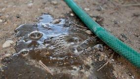 Agua que se escapa del agujero en una manguera almacen de metraje de vídeo
