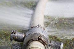 Agua que se escapa del agujero en una manguera Foto de archivo