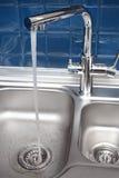 Agua que vierte del golpecito Imagen de archivo