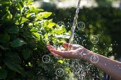 Agua que vierte en mano de la mujer con las fuentes de energía de los iconos para el desarrollo renovable, sostenible ecología imagen de archivo libre de regalías