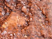 Agua sobre rocas rojas Imagenes de archivo