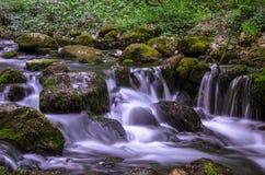 Agua a través de las piedras Imagenes de archivo