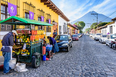 Agua volcano & colonial street, Antigua, Guatemala. Antigua, Guatemala - April 2, 2017: Fruit seller, colorful houses & Agua volcano in colonial city & UNESCO stock photos