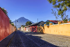 Agua volcano & colonial street, Antigua, Guatemala. Antigua, Guatemala - October 5, 2014: Old, colorful, painted houses & Agua volcano in colonial city & UNESCO stock photography