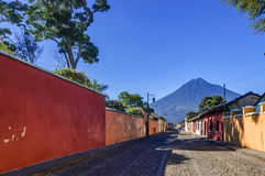 Agua volcano & colonial street, Antigua, Guatemala. Old, colorful, painted houses & Agua volcano in colonial city & UNESCO World Heritage Site of Antigua royalty free stock photos