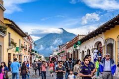 Agua volcano & tourists, Antigua, Guatemala. Antigua, Guatemala - July 24, 2016: Tourists walk in popular Calle del Arco near central park with view of Agua Stock Photos