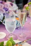 Agua y champán en la tabla de la boda Fotos de archivo libres de regalías