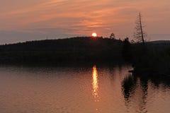 Agua y cielos anaranjados en la puesta del sol Foto de archivo libre de regalías