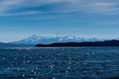 Agua y montañas capsuladas nieve en el fondo el lago Titicaca fotos de archivo