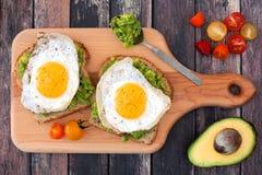 Aguacate, bocadillos abiertos del huevo en el tablero de paleta Imagen de archivo