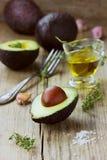 Aguacate con el aceite de oliva, tomillo de la hierba fotografía de archivo