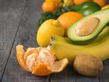 Aguacate, mandarinas, naranjas, kiwi y plátanos cortados en la tabla rústica del vintage Comida vegetariana Foto de archivo