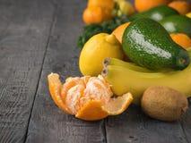 Aguacate, mandarinas, naranjas, kiwi y plátanos en la tabla rústica del vintage Comida vegetariana Foto de archivo