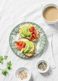 Aguacate, queso suave, tomates de cereza bocadillo y té con la leche en un fondo ligero, visión superior Bocado sano Imagen de archivo