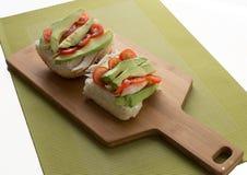 Aguacate, tomate y pollo en un rollo de pan abierto en el tablero de madera Imagenes de archivo