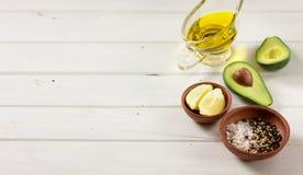 Aguacate y otros ingredientes para el guacamole de la salsa en la tabla foto de archivo