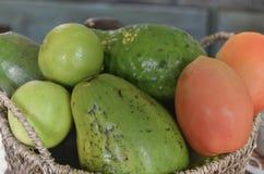 Aguacates frescos en una cesta con los tomates y las cales fotos de archivo libres de regalías