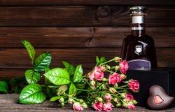 Aguardente, flores e um presente por uma noite romântica Imagens de Stock