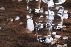 Aguardiente - bebida alcohólica, alcohol ilegal de la uva o vodka fuerte español tradicional, en vidrios en una tabla de madera v foto de archivo libre de regalías