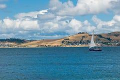 Aguas azules de la vela de lujo del yate a lo largo de una costa Foto de archivo