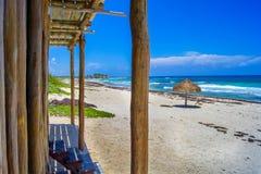 Aguas azules, paraguas y playa de la isla caribeña Foto de archivo