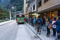 Passengers lining up for bus going up to Machu Picchu. Aguas Calientes, Peru - Sep 14, 2018: Passengers lining up at a terminal in Aguas Calientes for bus going royalty free stock photos