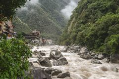 Aguas Calientes town. Landscape with powerful Urubamaba river on foreground in Peru royalty free stock photography