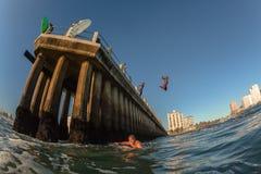 Aguas del océano que practican surf a nadadores de las personas que practica surf de Durban Pier Paddle Jump Imagenes de archivo
