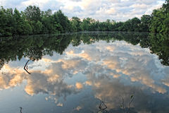 Aguas del pantano que reflejan las nubes de la mañana Fotografía de archivo