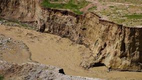Aguas fangosas que tallan el suelo de las colinas almacen de video