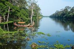 Aguas pacíficas y canoa camboyana Foto de archivo