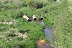 Aguas residuales ennegrecidas de plantas industriales y de las charcas inútiles que fluyen del extremo de la tubería a las fuente imagen de archivo